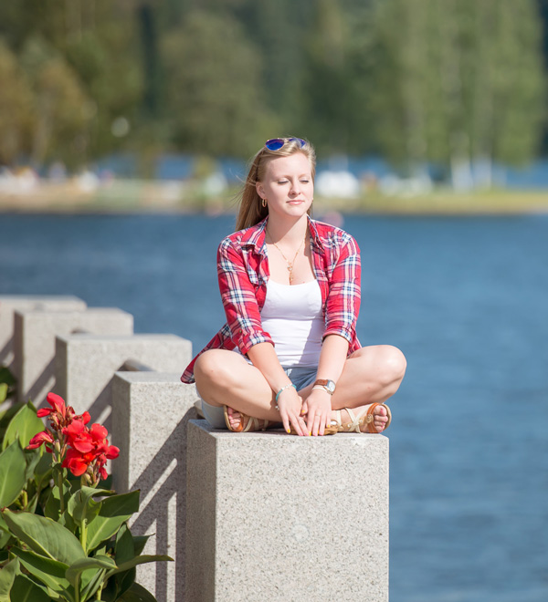 young adult sitting on pier