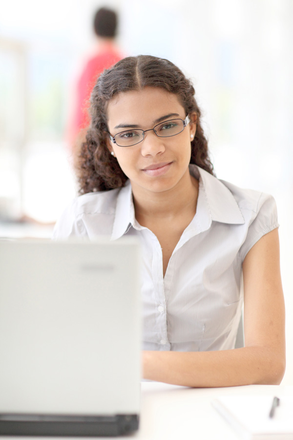 young adult sitting at laptop computer